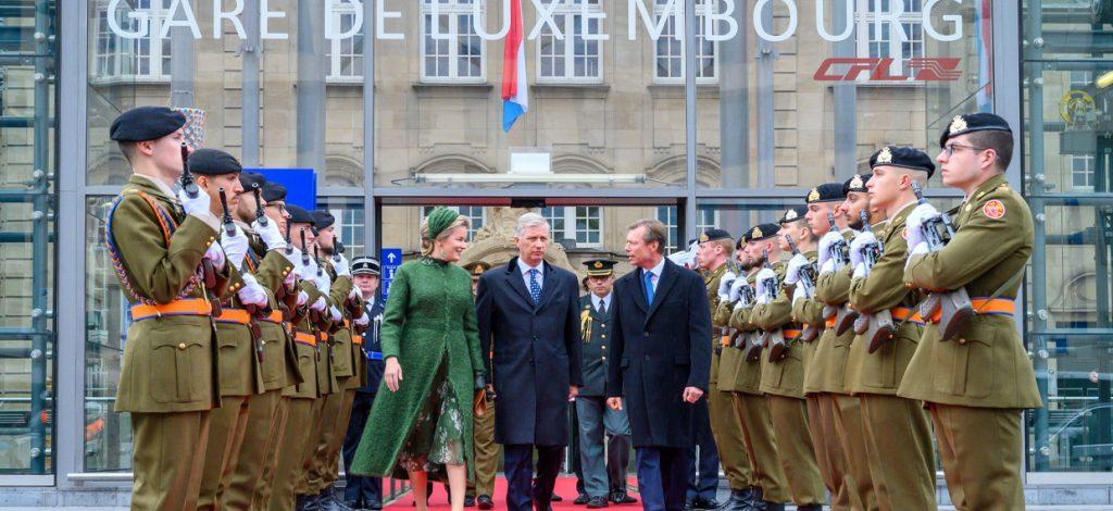 Les protagonistes marchent sur le tapis rouge, entourés de militaires au garde-à-vous.