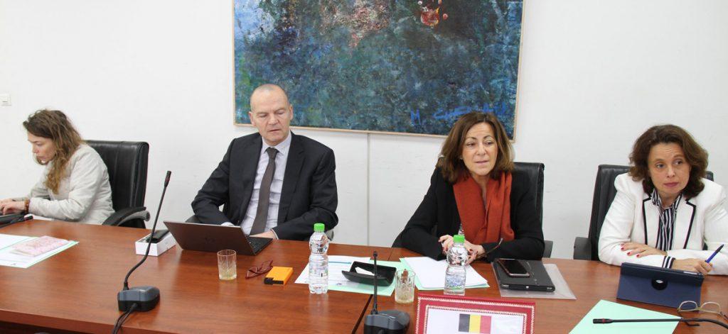 Les quatre intervenants sont assis côte à côte, à une table de réunion.