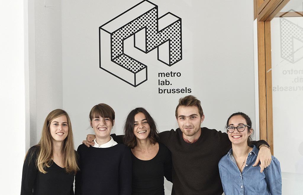5 teamleden poseren staand voor het logo van Metrolab Brussels
