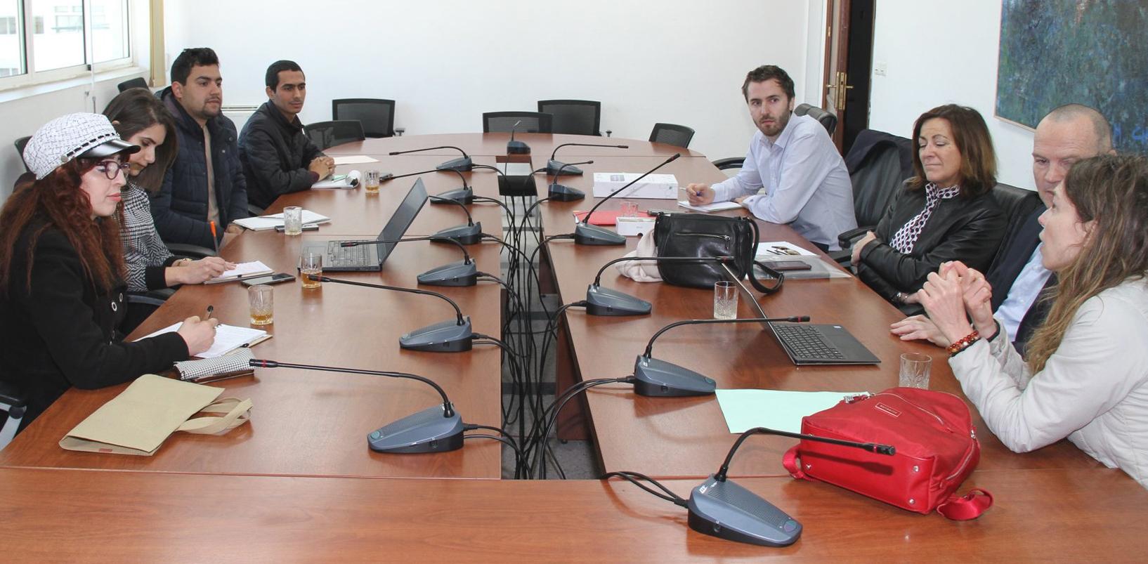 Les huit protagonistes sont assis autour d'une table de réunion.