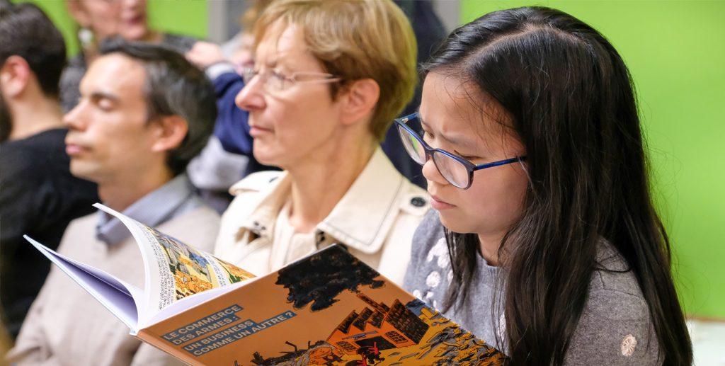 Une jeune lectrice parcourt la bande dessinée.