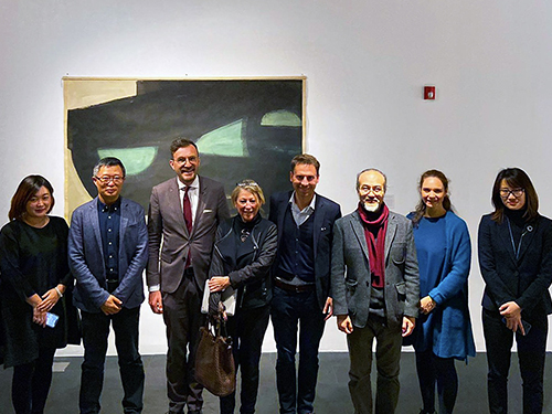The protagonists are pictured standing, in front of an artwork.