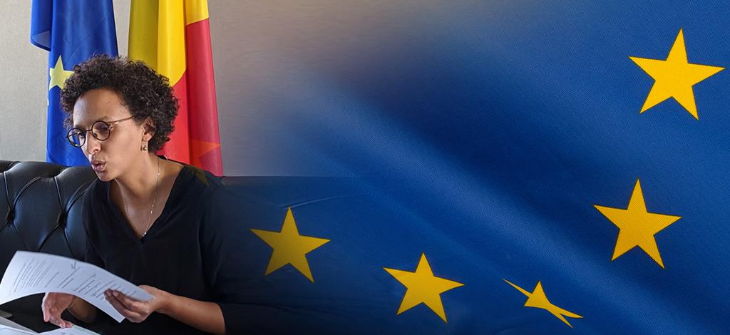 La Secrétaire d'État parle avec une feuille en main, assise devant les drapeaux européen et belge
