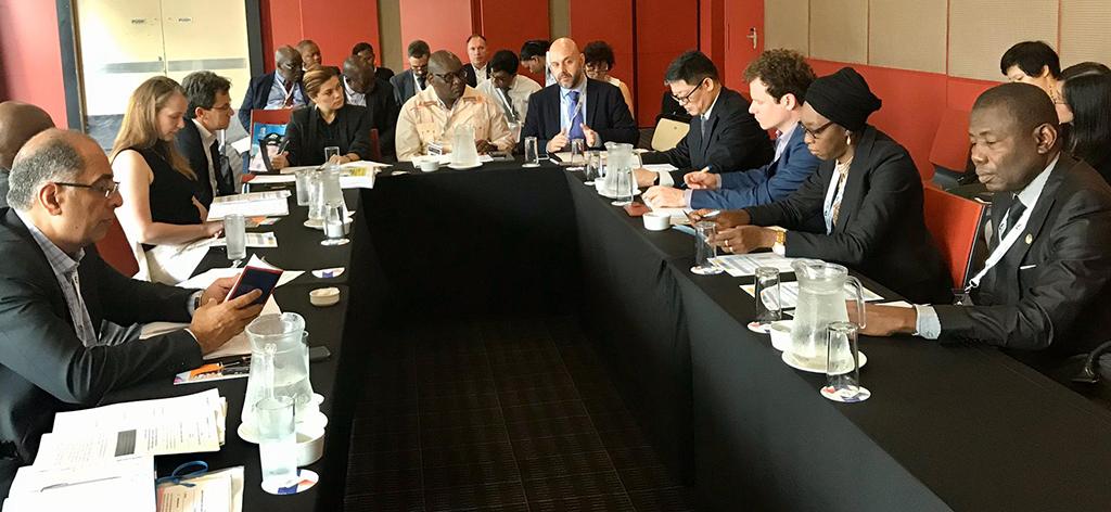 Les protagonistes sont assis autour d'une table de réunion.