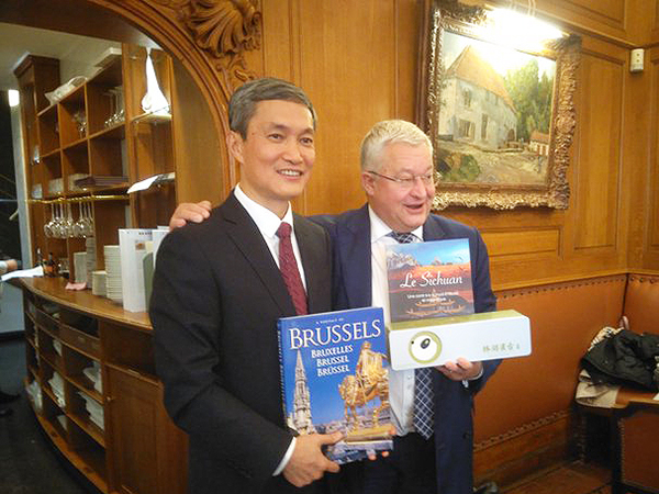 The two representatives pose with books on Brussels and Sichuan.