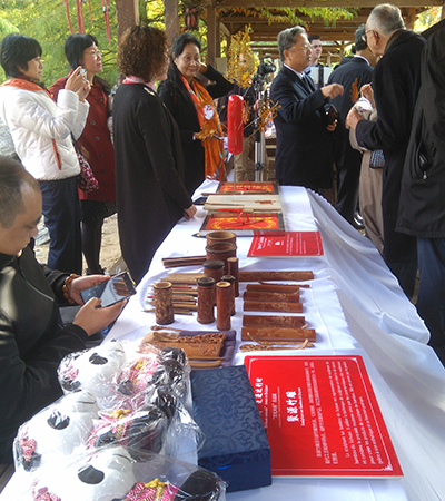 The Chinese representatives display traditional hand-crafted products on a table.