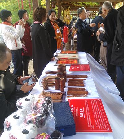 Chinese vertegenwoordigers stellen ambachtelijke voorwerpen tentoon op een tafel.