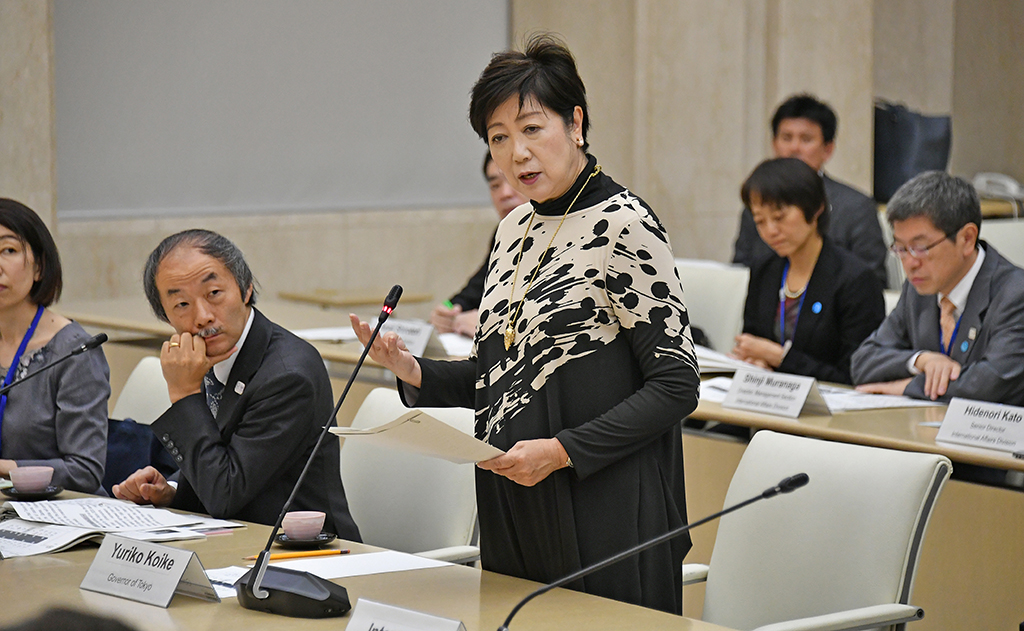 Yuriko Koike is pictured standing, giving a speech, surrounded by other participants.