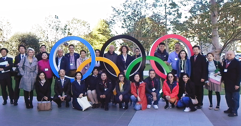 The participants pose around the Olympic rings.