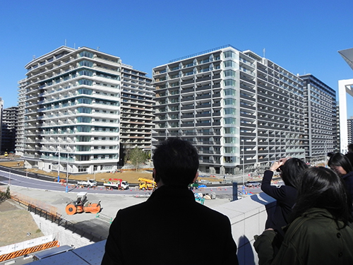 The visitors are shown looking at buildings.