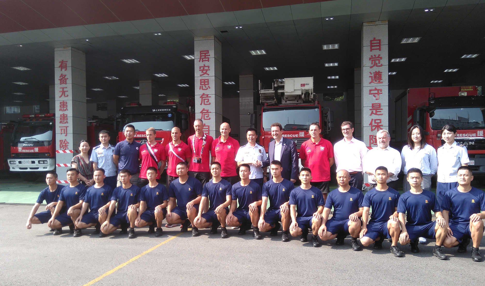 The Brussels and Chinese firemen pose in front of the fire station.