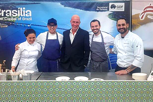 The representatives pose on the Brazilian food stand.