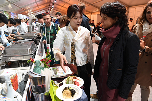 A Korean representative explains her country's cuisine to a member of the public visiting the Korean stand.