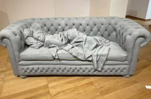 Grey sculpture of a child sleeping on a sofa