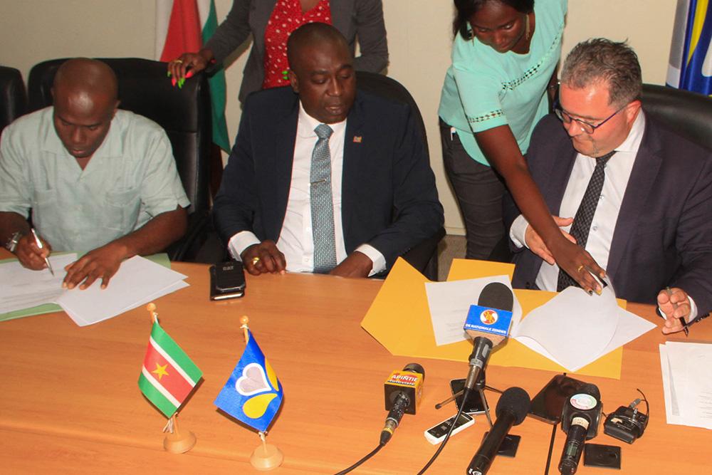 Christian Lamouline (SPRB), Edgar Dikan et un représentant du District de Paramaribo signent le MoU