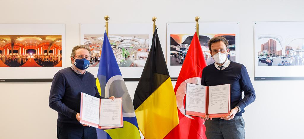 ALT-TAG : Les protagonistes, debout autour des drapeaux bruxellois, belge et stambouliote, présentent les documents signés.