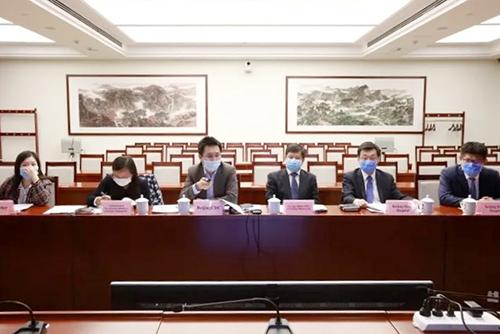 De deelnemers, met mondmasker, naast elkaar aan een tafel.