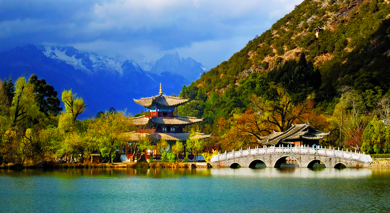Moon-Embracing Pavilion, lake and bridge at Black Dragon Lake Park in Lijiang, Yunnan Province, China, with the Jade Dragon snow mountain in the background.