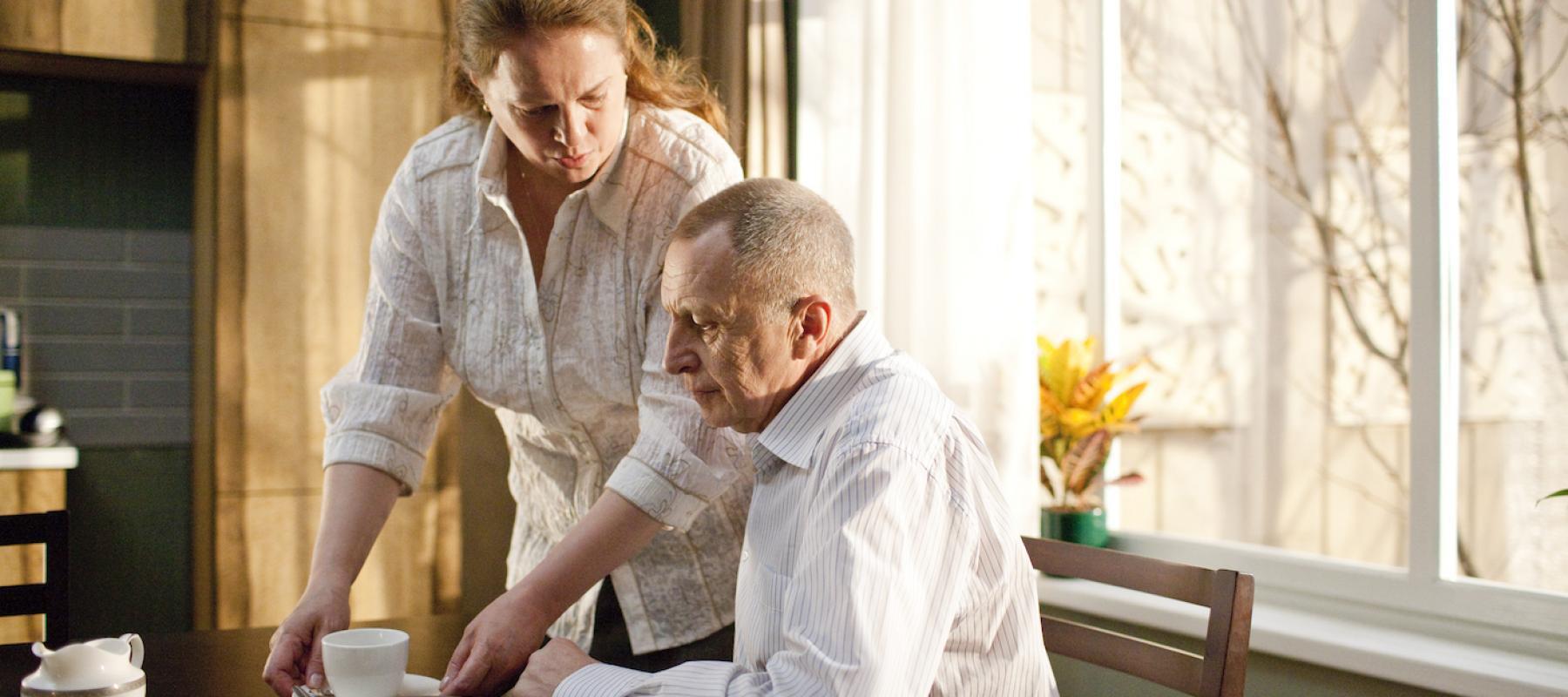 Femme debout et homme assis devant une fenêtre, image du film