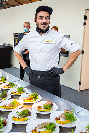 The chef, wearing an apron, in front of the dishes he prepared on the pass.