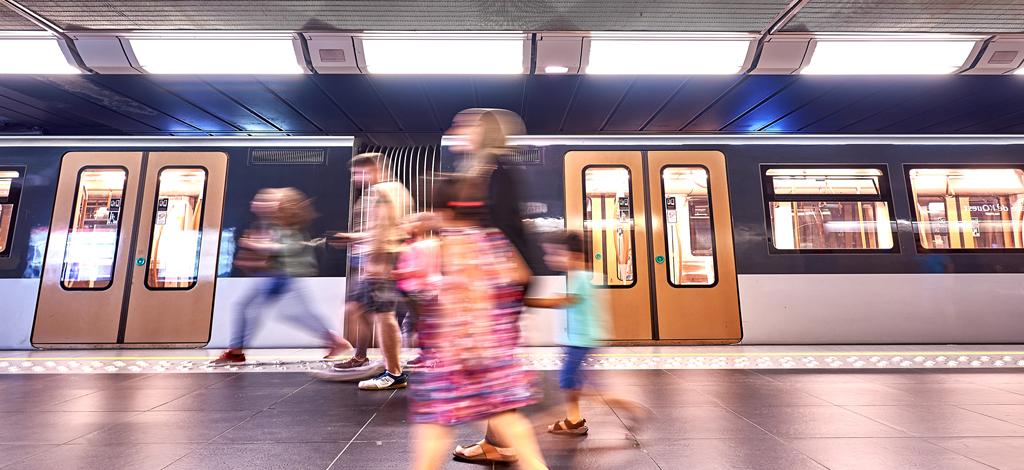 Rame de métro et usagers en mouvement sur le quai