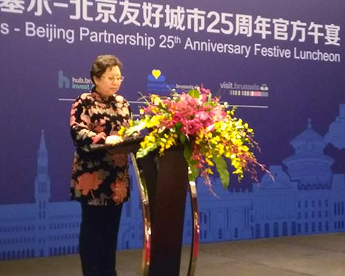 Wang Hong est debout face au pupitre orné d'un bouquet de fleurs jaunes et rouges.