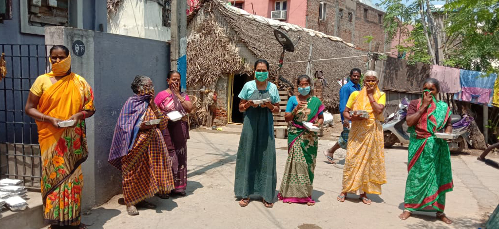 Indian women, waiting in line on the street, holding a receptacle.