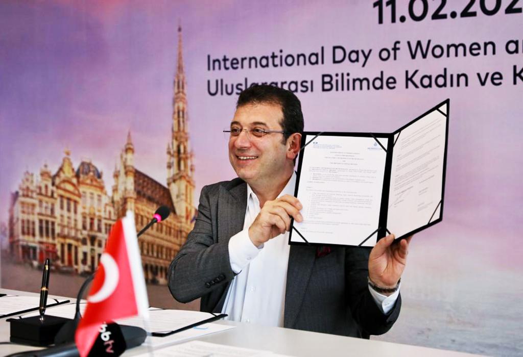 Le Maire, assis à un bureau, présente le document signé.
