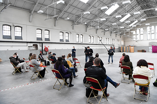 Seated journalists in the large interior space of the Manège building.