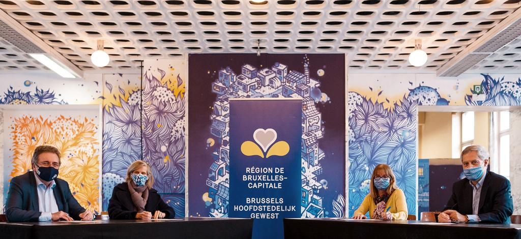 Les quatre protagonistes, masqués, assis à une table autour du logo de la Région bruxelloise