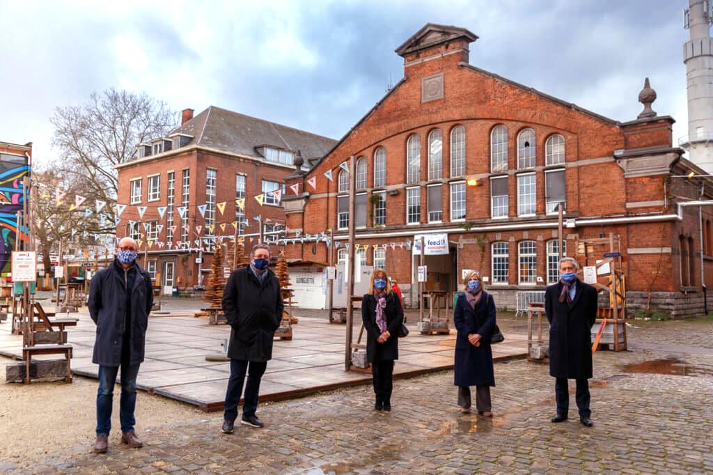 Les cinq protagonistes debout, masqués, devant le bâtiment