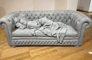 Sculpture grise d'un enfant allongé sur un divan
