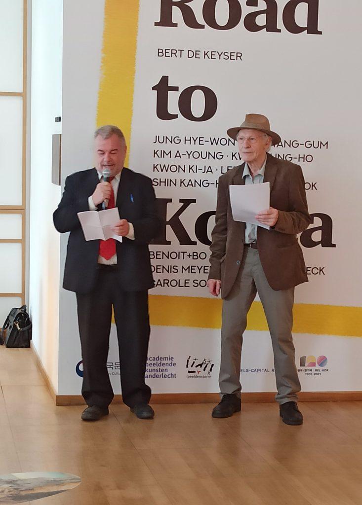 Les deux protagonistes, debout devant l'affiche de l'exposition