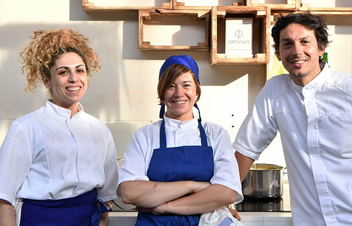 The three chefs, wearing their aprons and presenting their dishes.
