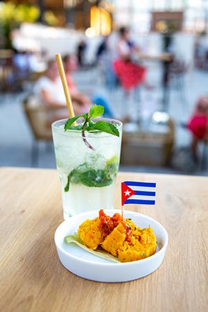 Glass of Cuban mojito and portion of surf & turf tamal.