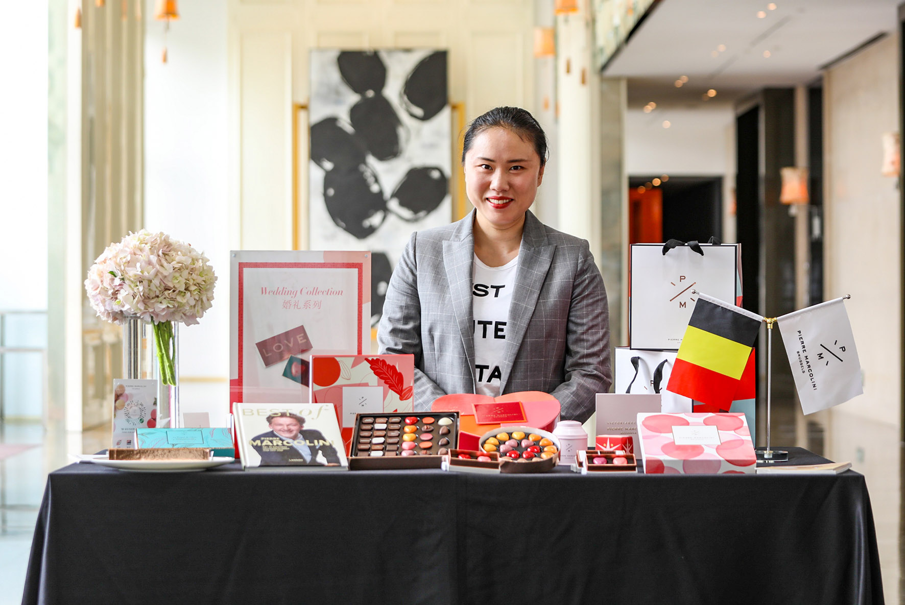 A Chinese woman standing behind a table with boxes of chocolate