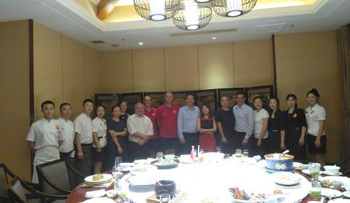 Les participants posent à côté de leur table bien garnie, en compagnie de l'équipe du restaurant.
