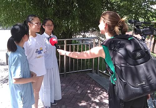 Trois étudiantes répondent aux questions de la journaliste dans le jardin de l'école.