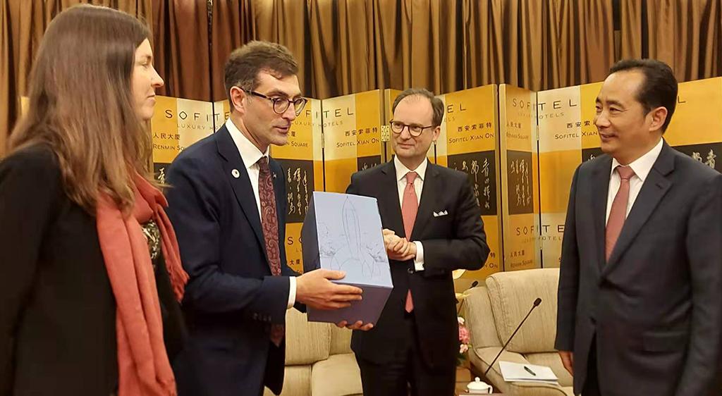Les protagonistes sont debout, M. Debroyer présente le cadeau à L. Mingyuan