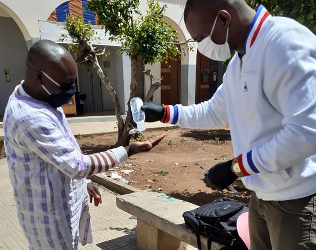 Un homme distribue du gel hydroalcoolique à un autre.