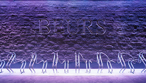 Bike racks in front of a wall, featuring the inscription BEURS