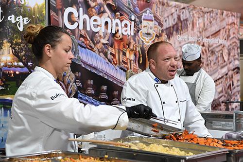 Cuisinière et cuisiniers dans les stands bulgare et indien.